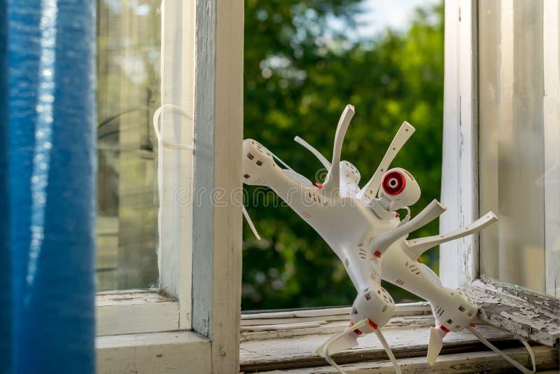 Quadcopter con la cámara de vídeo del foto/se pegó en la ventana imagen de archivo libre de regalías