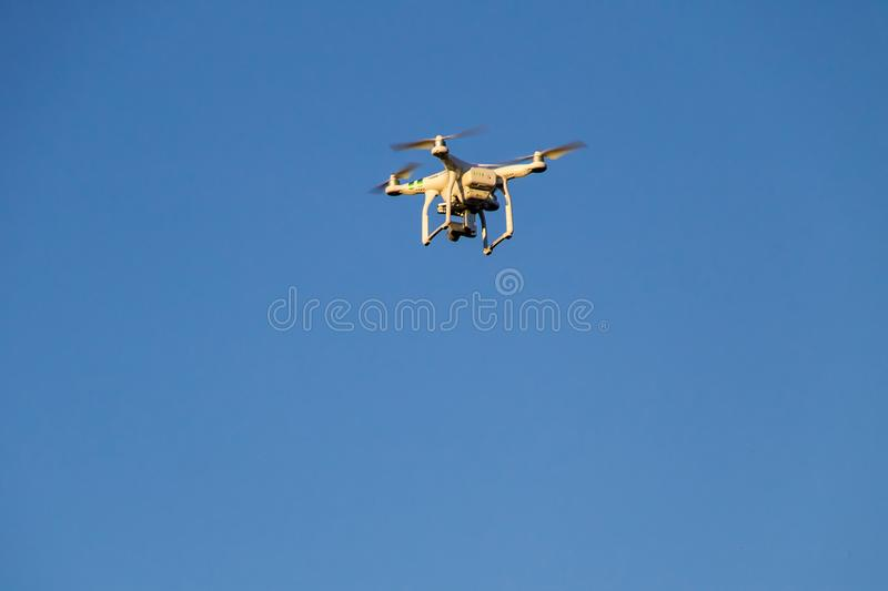 Quadcopter drone with the camera hovering in blue sky royalty free stock photography