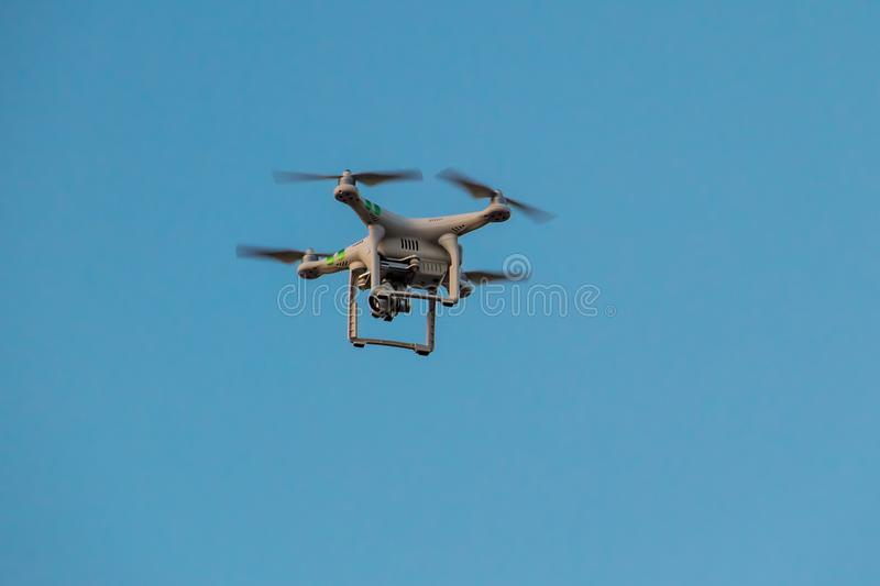 Quadcopter drone with the camera hovering in blue sky. Quadcopter drone with camera hovering in blue sky royalty free stock image