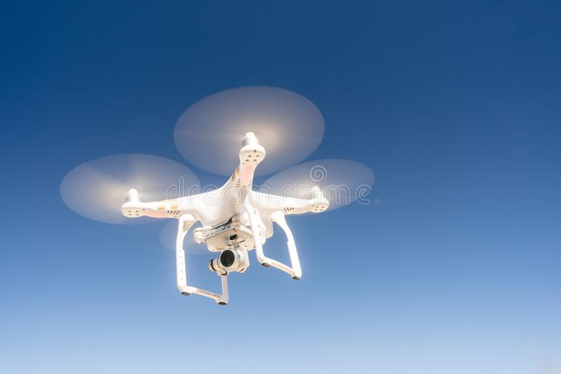 White Quadcopter Drone Flying Hoovering Blue Sky royalty free stock image