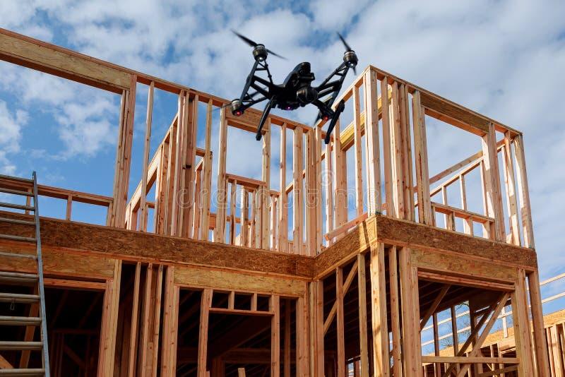 Quadcopter negro del abejón con la cámara que vuela sobre enmarcar casero de la construcción residencial contra foto de archivo libre de regalías
