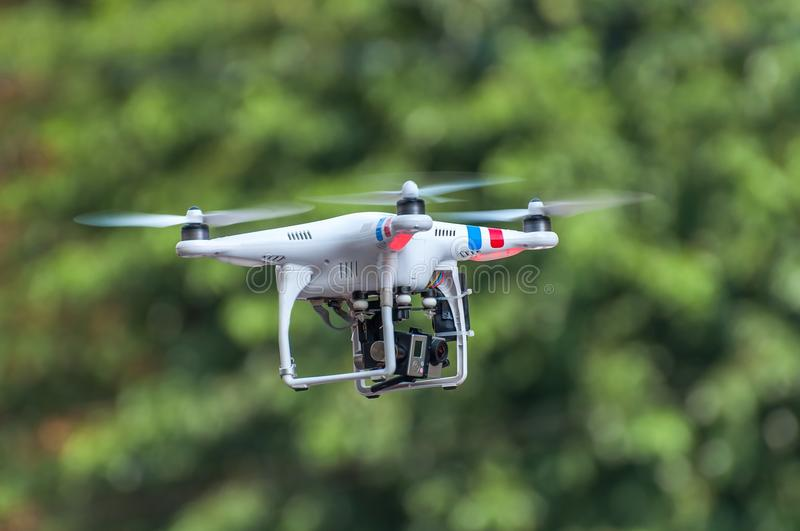 Quadcopter, quadrotor, drone on a green background. The unmanned radio-controlled aircraft flying on a green background of foliage stock photo