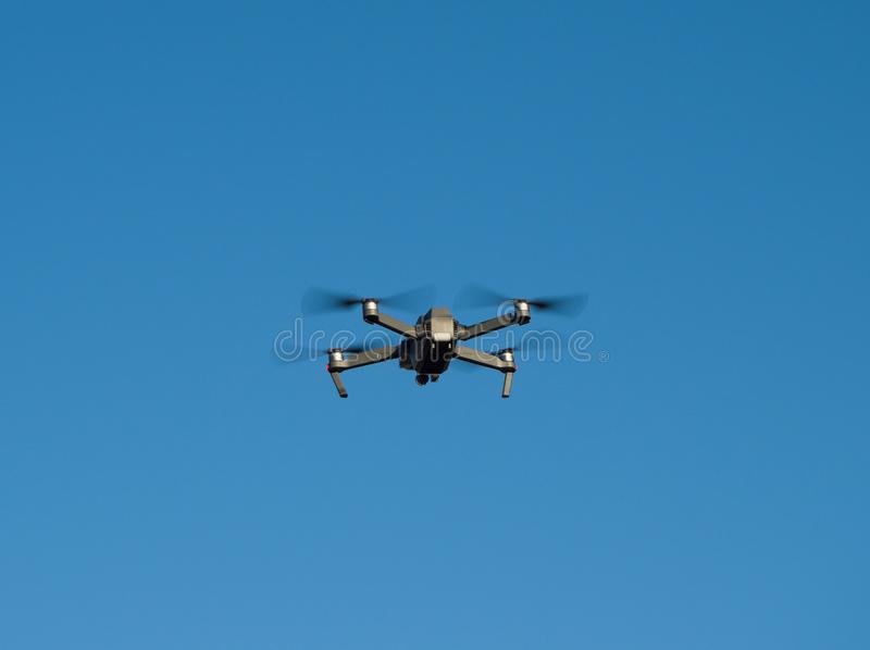 Quadcopter or quadrotor helicopter flying. High at blue sky background royalty free stock photos