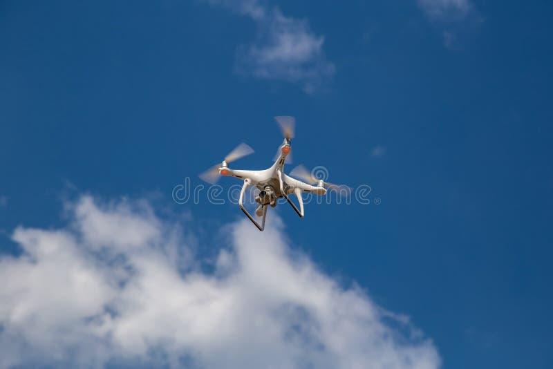 Quadcopter in volo contro un cielo blu ronzio fotografie stock