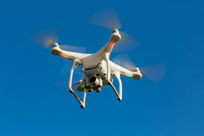 Quadcopterhommel die in blauwe hemel vliegen stock foto