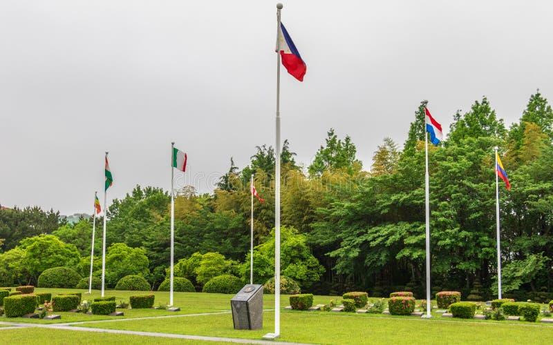 Quadrado central com as bandeiras de países participados dentro dos United Nations UNO Memorial Cemetery da Guerra da Coreia em S imagens de stock