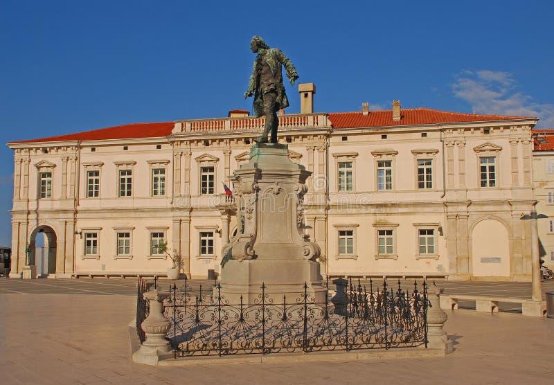 Quadrado de Tartini em Piran com a estátua de Giuseppe Tartini na construção do meio & de cargo no governo no fundo imagens de stock royalty free