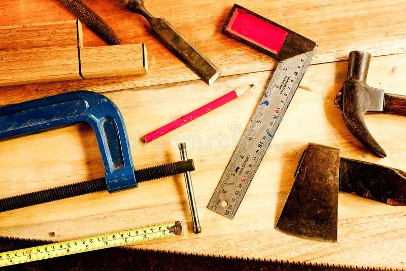 Quadrado do operador, lápis de madeira, martelo, serra, braçadeira, formão, torno, fita métrica, arquivo para o carpinteiro na ma foto de stock