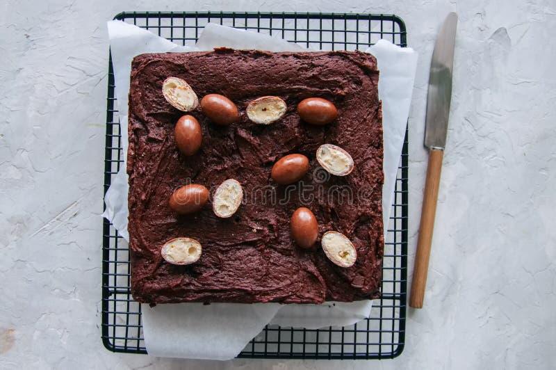 Quadrado escuro da brownie do chocolate em uma cremalheira de fio decorada com crea imagens de stock royalty free