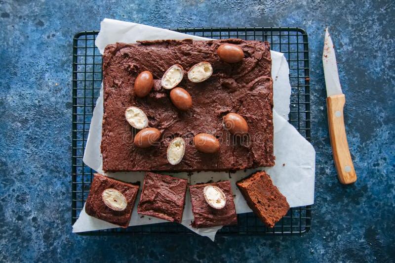 Quadrado escuro da brownie do chocolate em uma cremalheira de fio decorada com crea fotos de stock