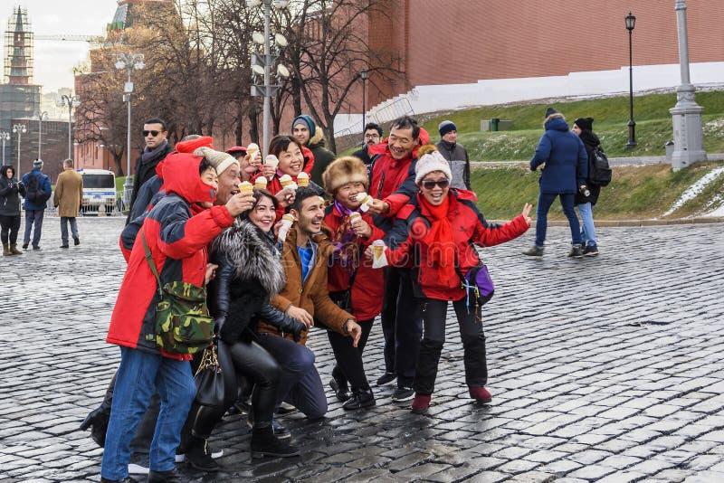 Quadrado vermelho Um grupo de turistas alegres e os viajantes são fotografados com um gelado delicioso na memória de Rússia foto de stock