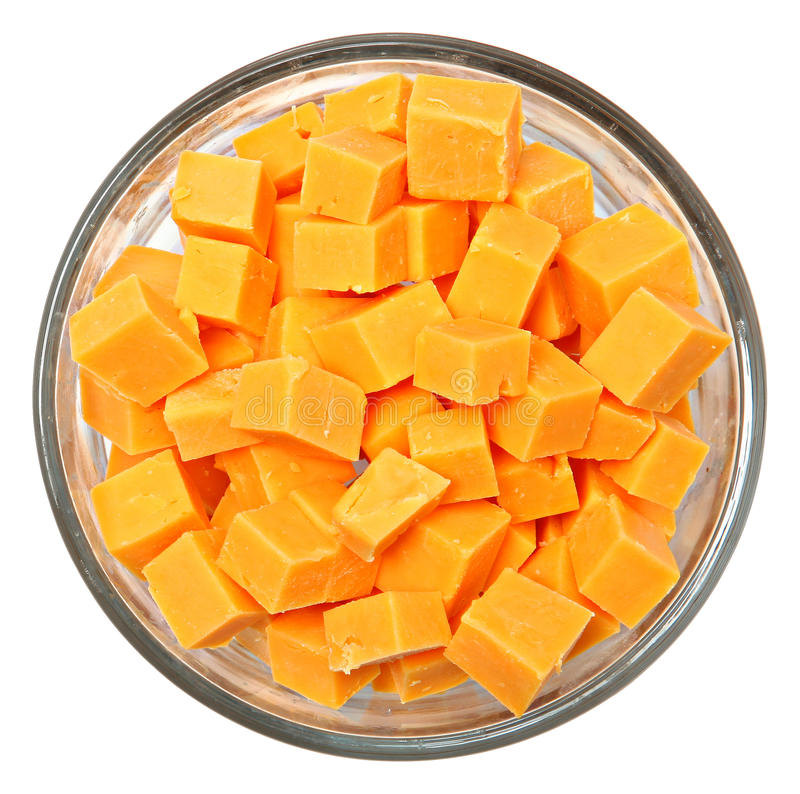 Quadrados cortados do queijo cheddar na bacia sobre o branco fotos de stock