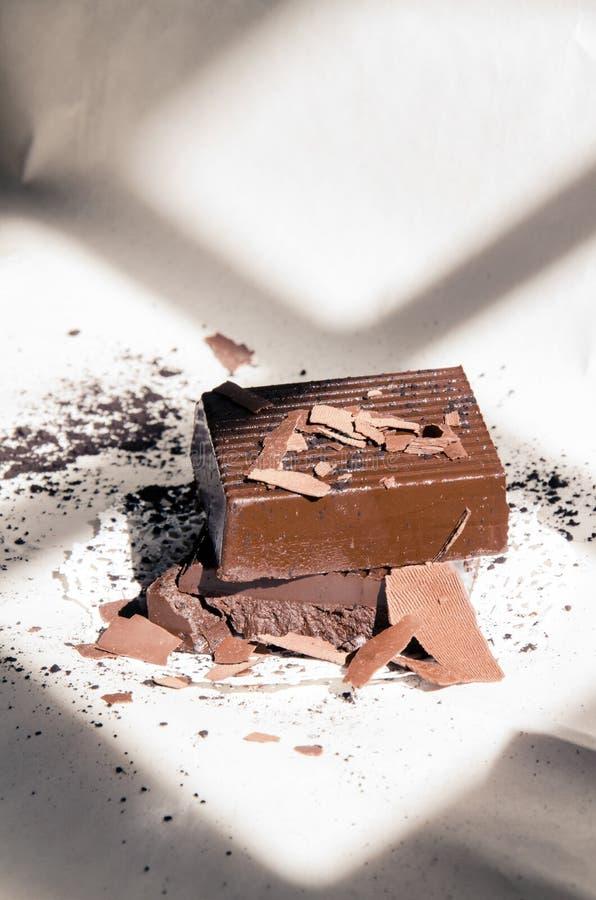 Quadrados escuros do chocolate empilhados em um fundo sombreado Minimalistic imagem de stock royalty free