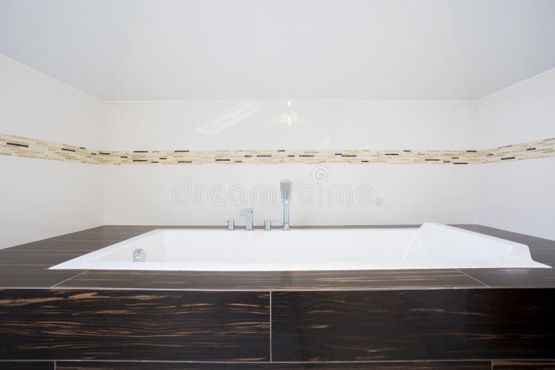 Quadratische Badewanne quadratische badewanne innerhalb des hellen badezimmers stockfoto