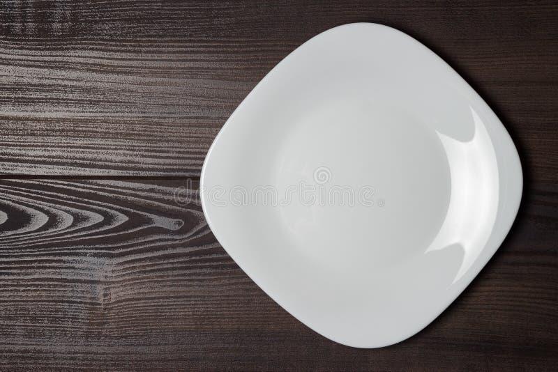 Quadratische Platte auf der hölzernen Tabelle stockfotos