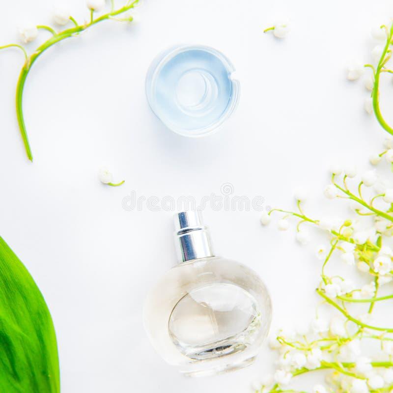 Quadratische Schönheitskonzeptkarte Flache Lage mit der kugelförmigen Parfümflasche umgeben durch frische Maiglöckchen, Könnenlil stockfotografie