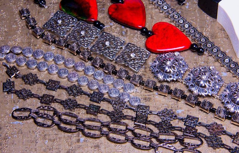 Quadratische und runde silberne Schieberperlen, Ketten und rote Herzen assembed in Armbänder stockfotografie