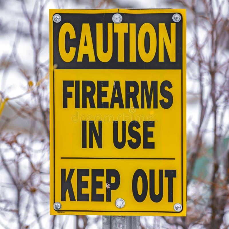 Quadratischer Abschluss oben eines gelben Zeichens, das liest, die gebräuchlichen Vorsicht-Feuerwaffen halten ab stockfotos