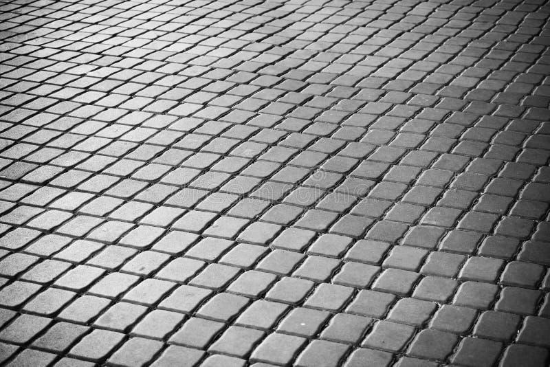 Quadratischer Gehweg des Mörserblogs Schwarzweiss vom abstrakten Hintergrund Minimalismus architecrure Details des modernen Muste stockfotografie