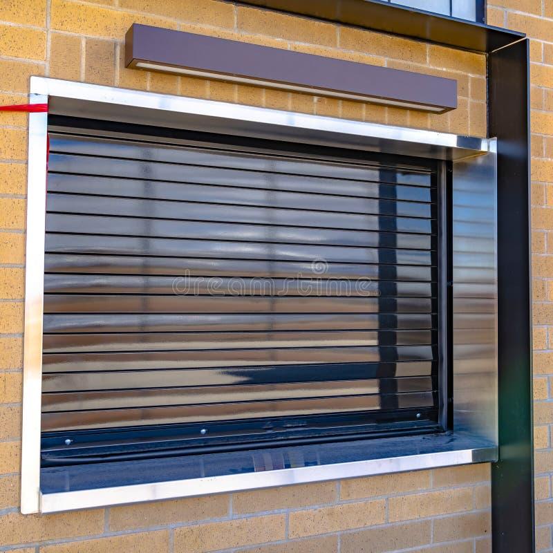 Quadratischer Rahmen Abschluss oben eines Geb?udes mit glattem industriellem Rollenfensterladen auf dem Fenster lizenzfreie stockbilder
