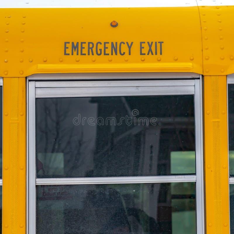 Quadratisches Äußeres eines gelben Schulbusses mit einem Abschluss herauf Ansicht seines Glasfensters stockfotografie