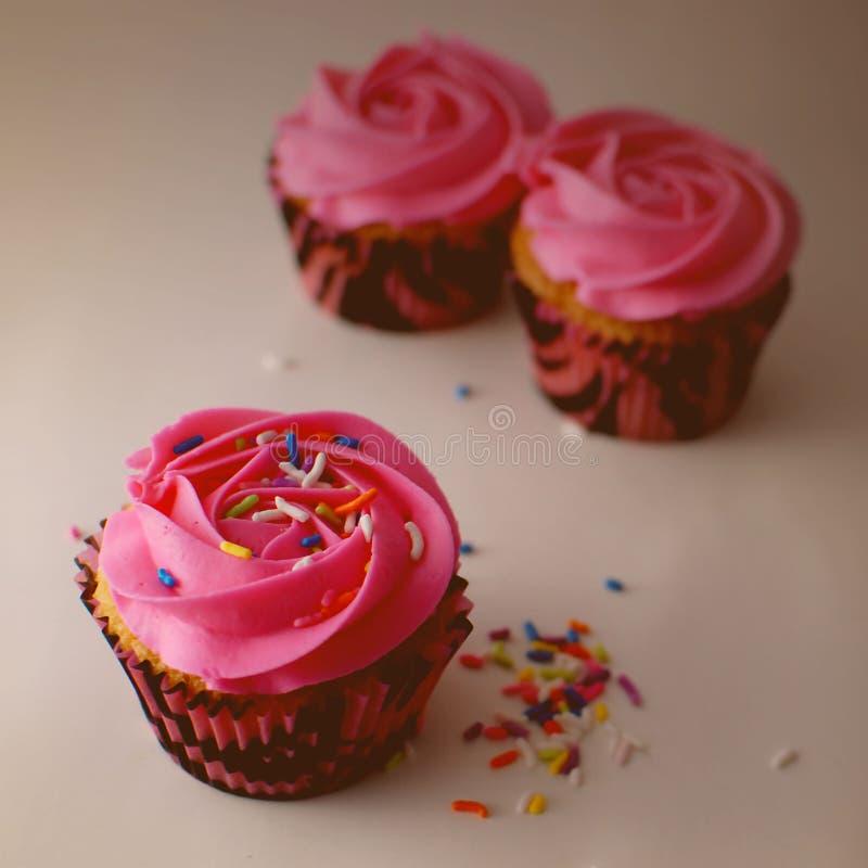 Quadratisches Bild von drei kleinen Kuchen mit dem rosa Bereifen und buntes besprüht mit Seitenbeleuchtungs- und Weinlesefilter lizenzfreies stockbild