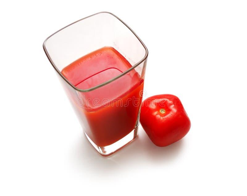 Quadratisches Glas mit Saft und suare Tomate lizenzfreie stockbilder