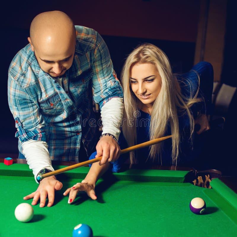 Quadratisches Porträt von schönen Paaren spielt Billard auf dem Pool t lizenzfreie stockfotos