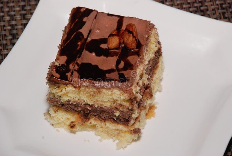 Quadratisches Stück des Kuchens mit Schokolade und Mandel auf der weißen Platte stockfotos
