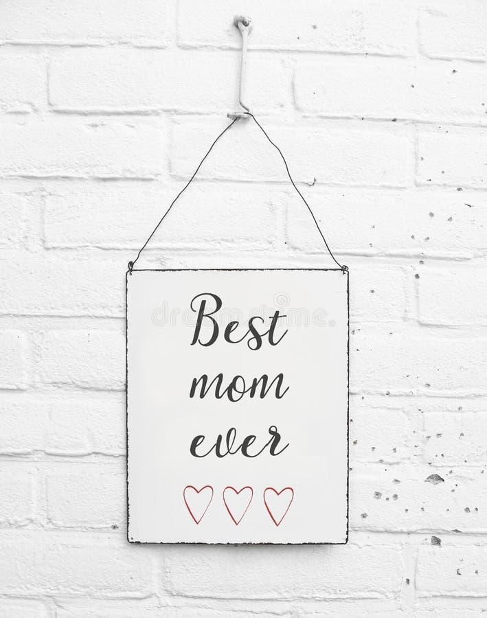 Quadrato bianco di piastra metallica sul fondo bianco dei mattoni - con il giorno di madri felice del testo per il papà della mam fotografie stock