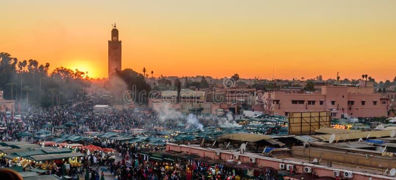 Quadrato del mercato di EL-Fnaa della moschea e di Jemaa di Koutoubia al tramonto fotografie stock libere da diritti