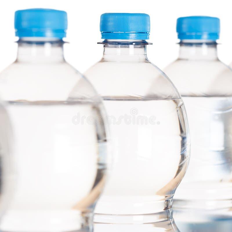 Quadrato delle bottiglie della bottiglia di acqua isolato su bianco fotografia stock