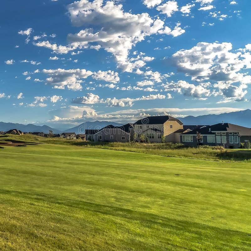Quadrato Fairway di un campo da golf in vista di case e montagne sullo sfondo immagine stock libera da diritti