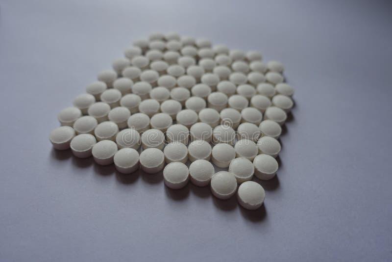 Quadrato fatto di piccole compresse bianche della vitamina K fotografia stock