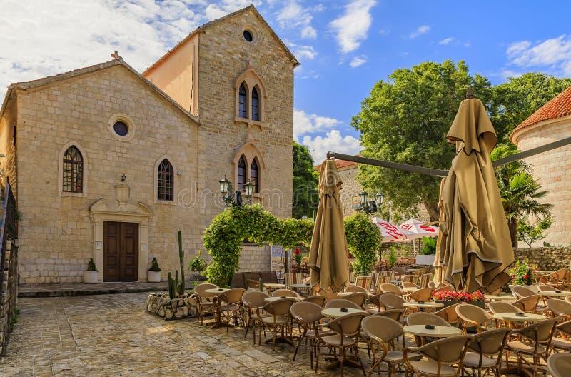 Quadrato pittoresco con un ristorante e la chiesa di trinità santa nella vecchia città in Budua Montenegro nei Balcani immagini stock