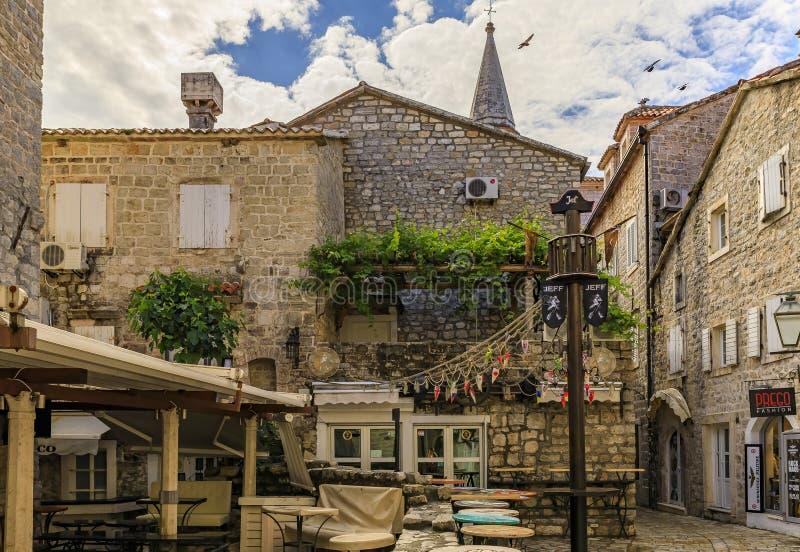 Quadrato pittoresco con un ristorante ed i negozi nella vecchia città in Budua Montenegro nei Balcani sul mare adriatico fotografie stock