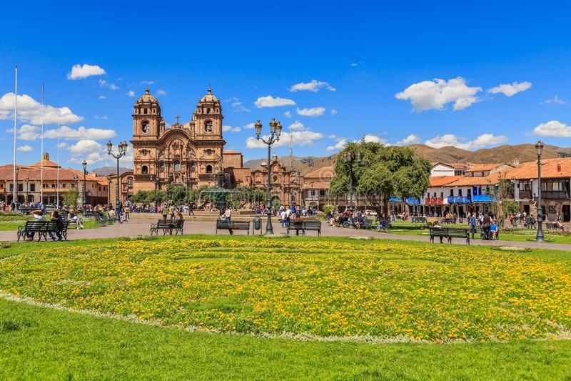 Quadrato principale di Plaza de Armas con la cattedrale e fiori gialli in priorità alta, Cuzco, Perù fotografia stock