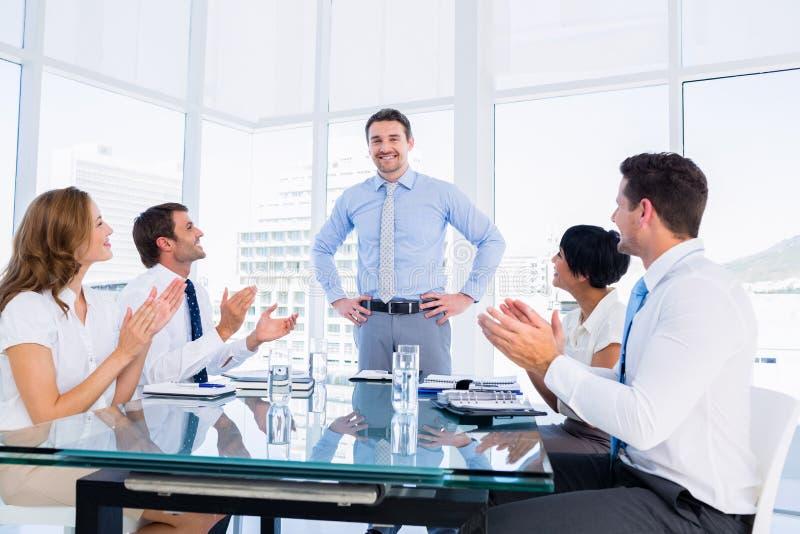 Quadri che applaudono intorno alla tavola di conferenza immagine stock