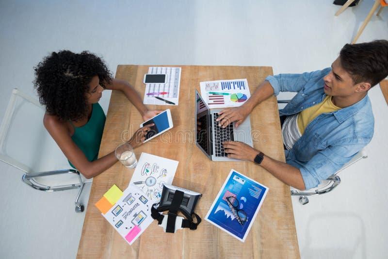 Quadri maschii e femminili che lavorano nell'ufficio immagini stock