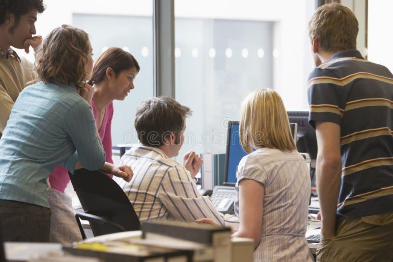 Quadri multietnici intorno al collega che per mezzo del computer fotografia stock