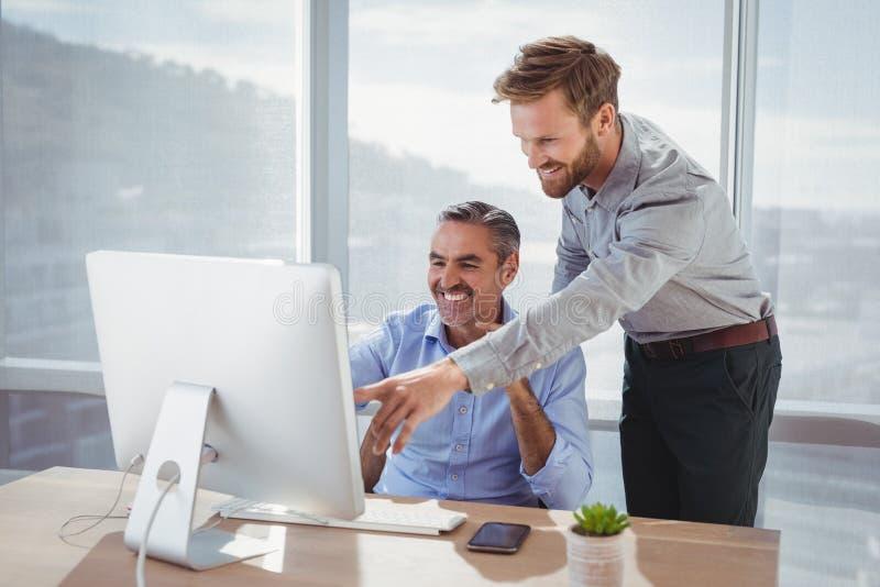 Quadri sorridenti che discutono sopra il personal computer allo scrittorio fotografie stock libere da diritti