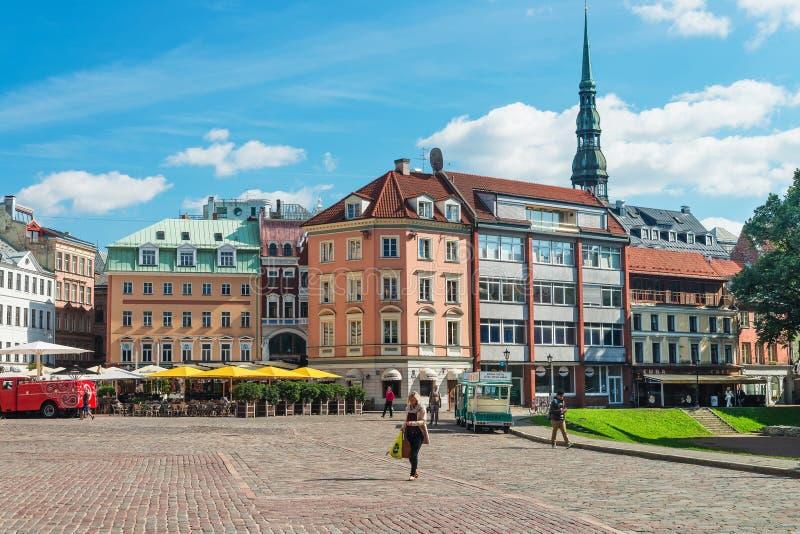 Quadrieren Sie mit Leuten und Helm von St. Peter Church Riga lizenzfreies stockfoto
