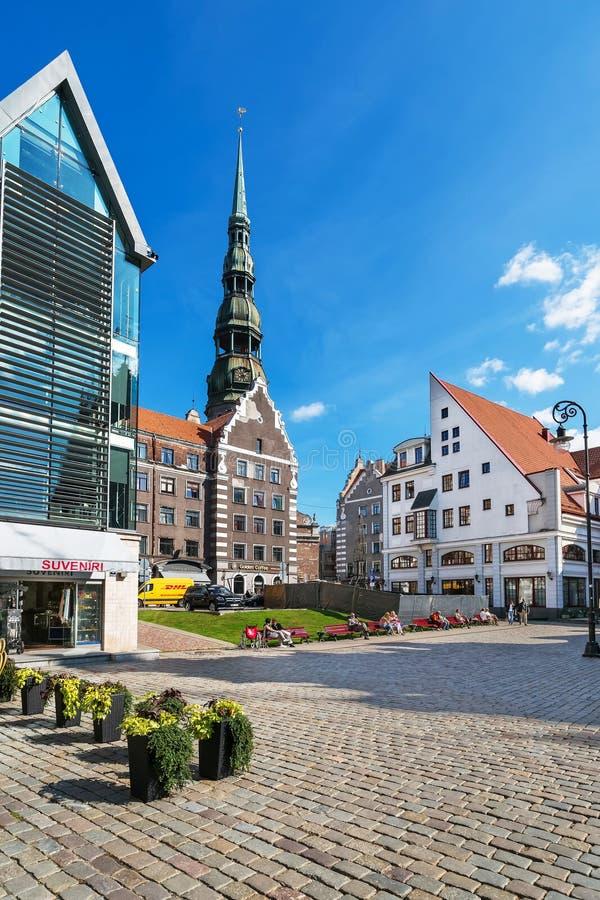 Quadrieren Sie mit Leuten und Helm von St. Peter Church Riga stockbild