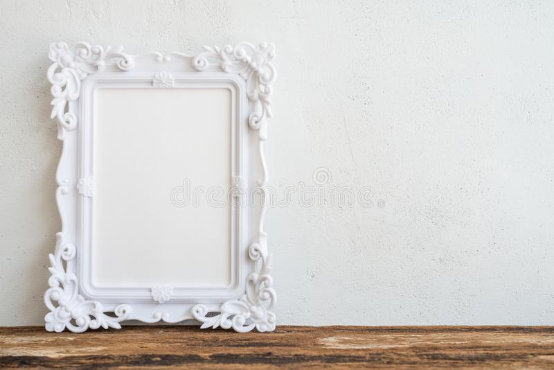 Quadro branco da foto do vintage na tabela de madeira velha sobre os vagabundos brancos da parede fotografia de stock