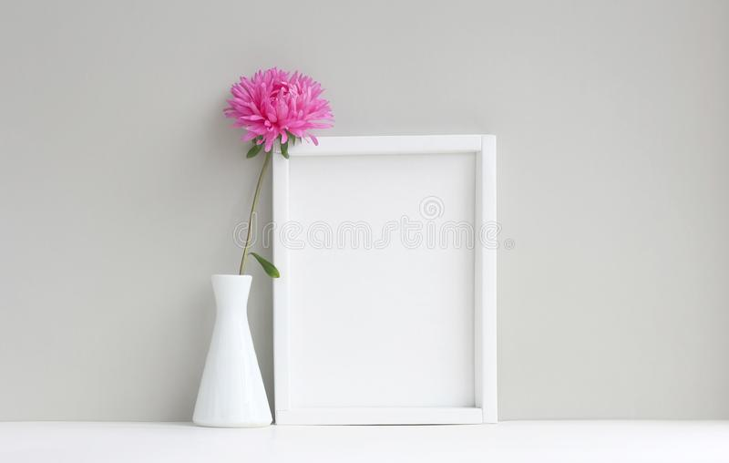 Quadro branco, modelo vazio, ao lado do vaso com áster cor-de-rosa foto de stock royalty free