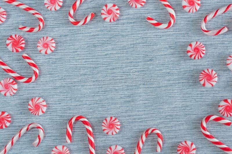 Quadro colocado liso de bastões de doces do Natal e de doces do redemoinho da pastilha de hortelã fotografia de stock