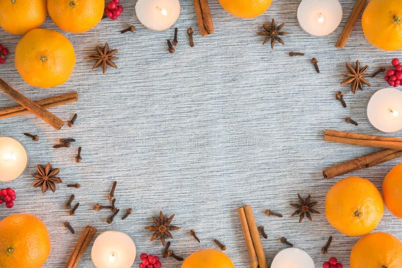 Quadro colocado liso do Natal das laranjas, das velas, e das especiarias imagem de stock