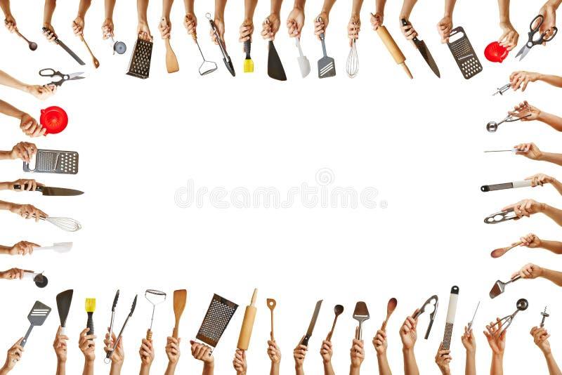 Quadro com as mãos que guardam muitas ferramentas da cozinha imagem de stock