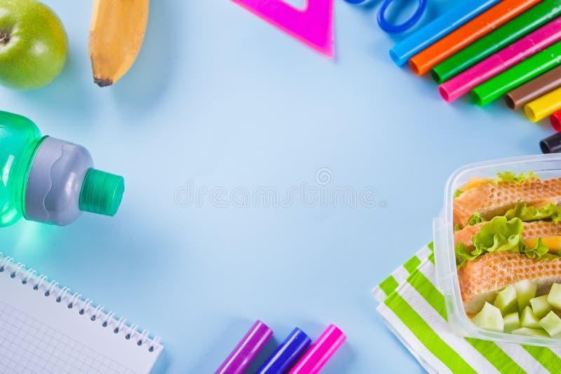 Quadro com canetas com ponta de feltro coloridas, caderno, maçã verde, sanduíche no fundo azul Conceito do estudante ou do aluno fotografia de stock