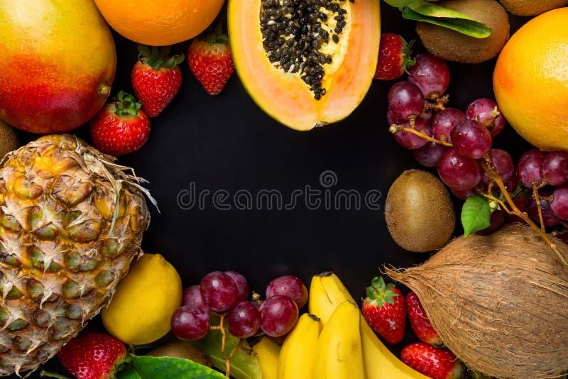 Quadro com espaço da cópia das laranjas sazonais frescas Kiwi Bananas Lemons tropicais e do verão dos frutos do abacaxi da papaia fotografia de stock royalty free
